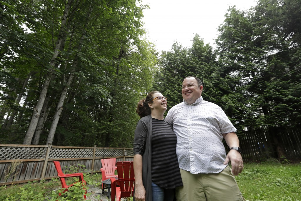 In this photo taken Friday, Aug. 2, 2019, Amy and Jason Ritchie stand in the backyard of their home, adjacent to a forest of conifer and deciduous tre...