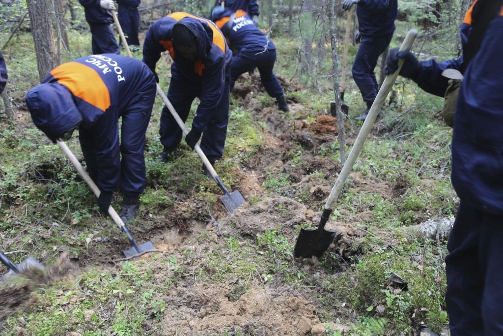 In this photo provided by Ministry of Emergency Situations of Krasnoyarsk Region on Saturday, Aug. 3, 2019, Emergency Situations employee dig a trench...