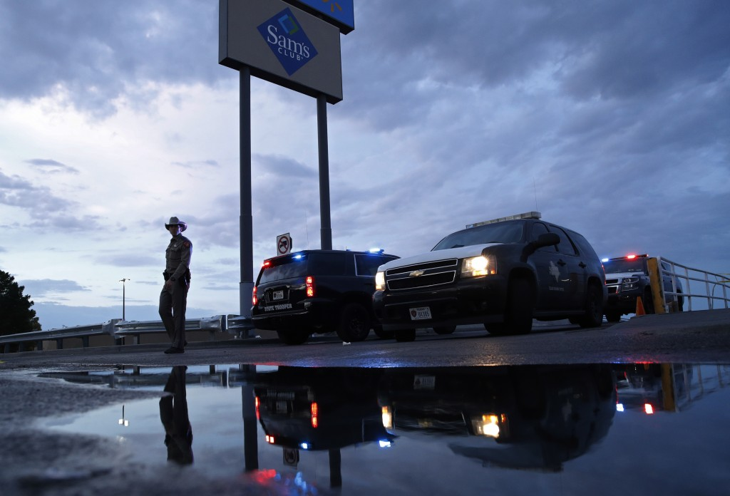Law enforcement officials block a road at the scene of a mass shooting at a shopping complex Sunday, Aug. 4, 2019, in El Paso, Texas. (AP Photo/John L...
