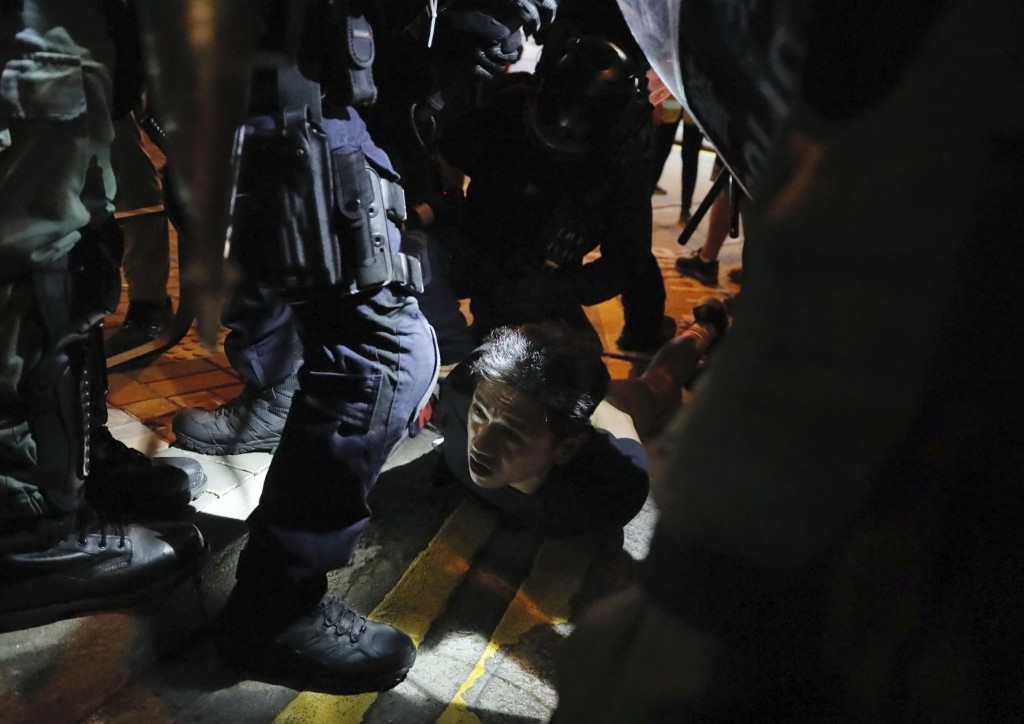 A man is detained by police during street protests in Hong Kong on Saturday, Aug. 3, 2019. Hong Kong protesters removed a Chinese national flag from i...