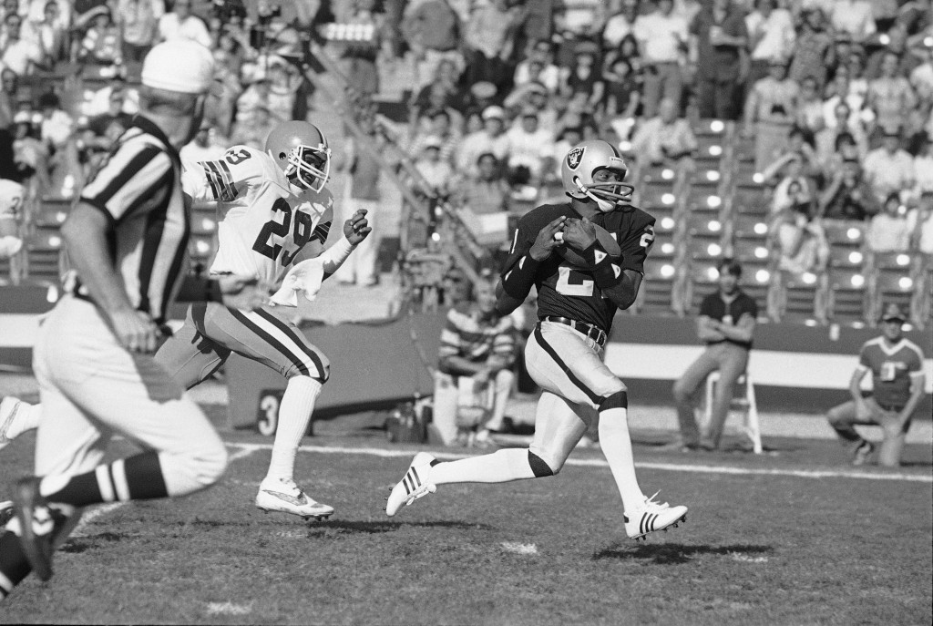FILE - In this Jan. 8, 1983, file photo Los Angeles Raiders wide receiver Cliff Branch, right, catches a pass from quarterback Jim Plunkett for a 64-y...