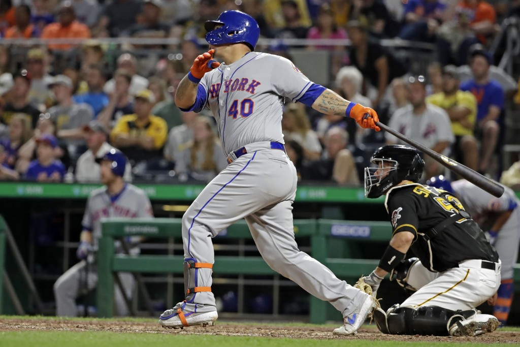 New York Mets' Wilson Ramos follows through on a two-run home run off Pittsburgh Pirates relief pitcher Kyle Crick during the eighth inning of a baseb