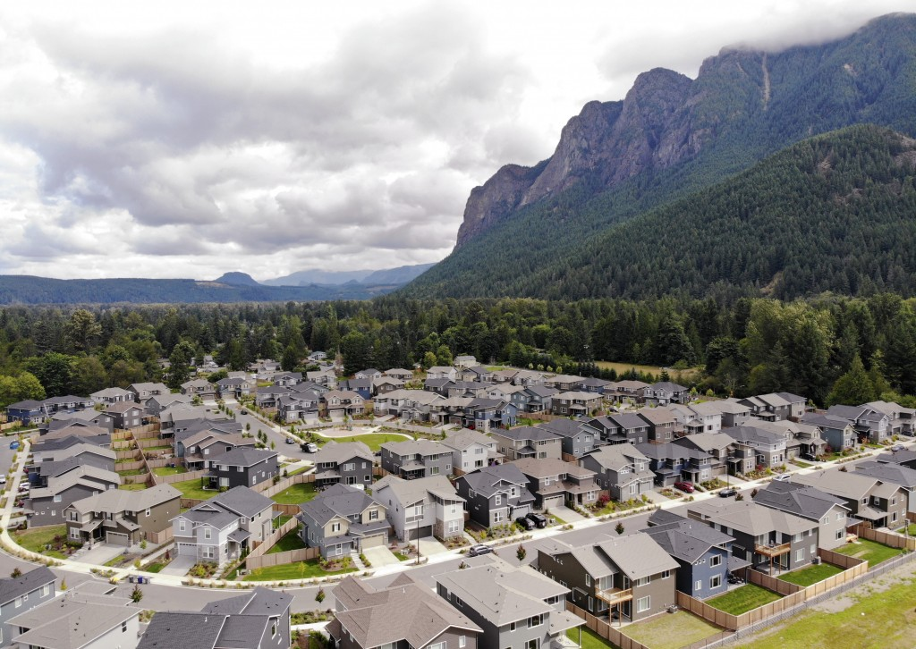 In this photo taken July 24, 2019, a development of houses stand next to a forest and in view of Mt. Si in the Cascade foothills of North Bend, Wash. ...