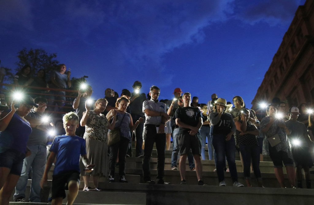 People attend a vigil for victims of the shooting Saturday, Aug. 3, 2019, in El Paso, Texas. A young gunman opened fire in an El Paso, Texas, shopping