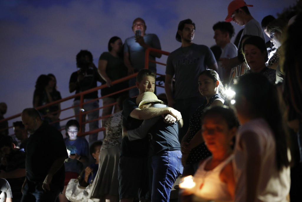 People embrace during a vigil for victims of the shooting Saturday, Aug. 3, 2019, in El Paso, Texas. A young gunman opened fire in an El Paso, Texas,