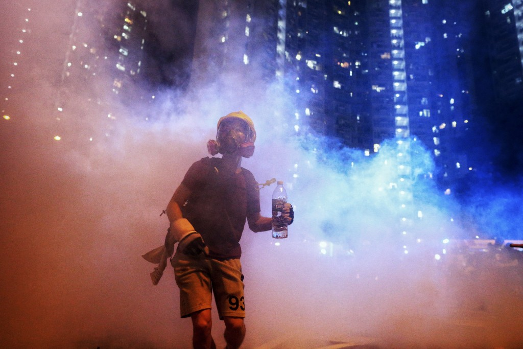 A protester stands in the midst of tear gas during confrontation with police in Hong Kong during the early hours of Sunday, Aug. 4, 2019. Hong Kong pr...