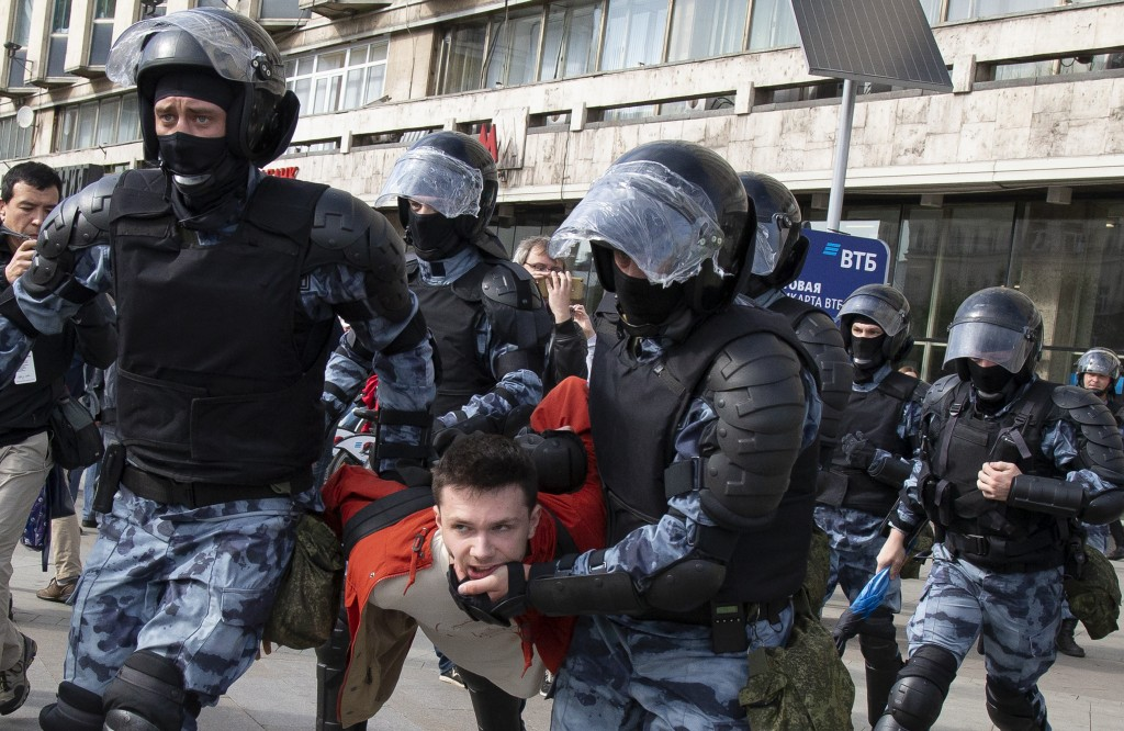 Police officers detain a protestor, during an unsanctioned rally in the center of Moscow, Russia, Saturday, Aug. 3, 2019. Moscow police detained more