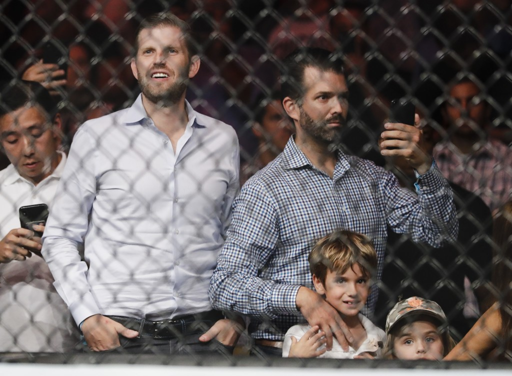 Eric Trump, left, and Donald Trump Jr., right, wait for the start of a welterweight mixed martial arts bout between Colby Covington and Robbie Lawler