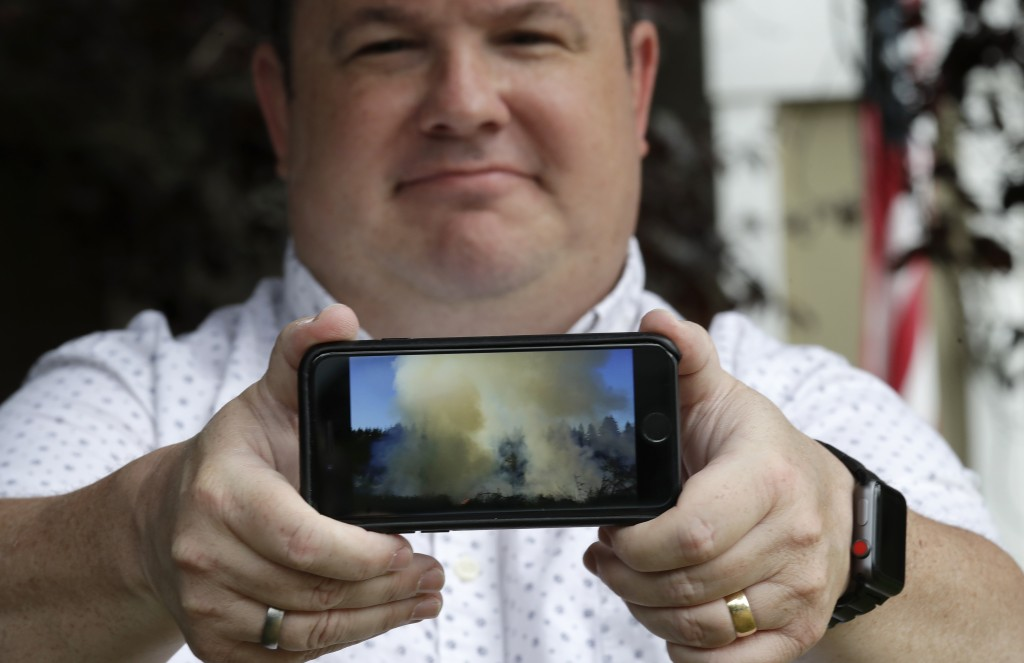 In this photo taken Friday, Aug. 2, 2019, Jason Ritchie holds his phone with a photo he took of a wildfire behind his home four years earlier, in Samm...