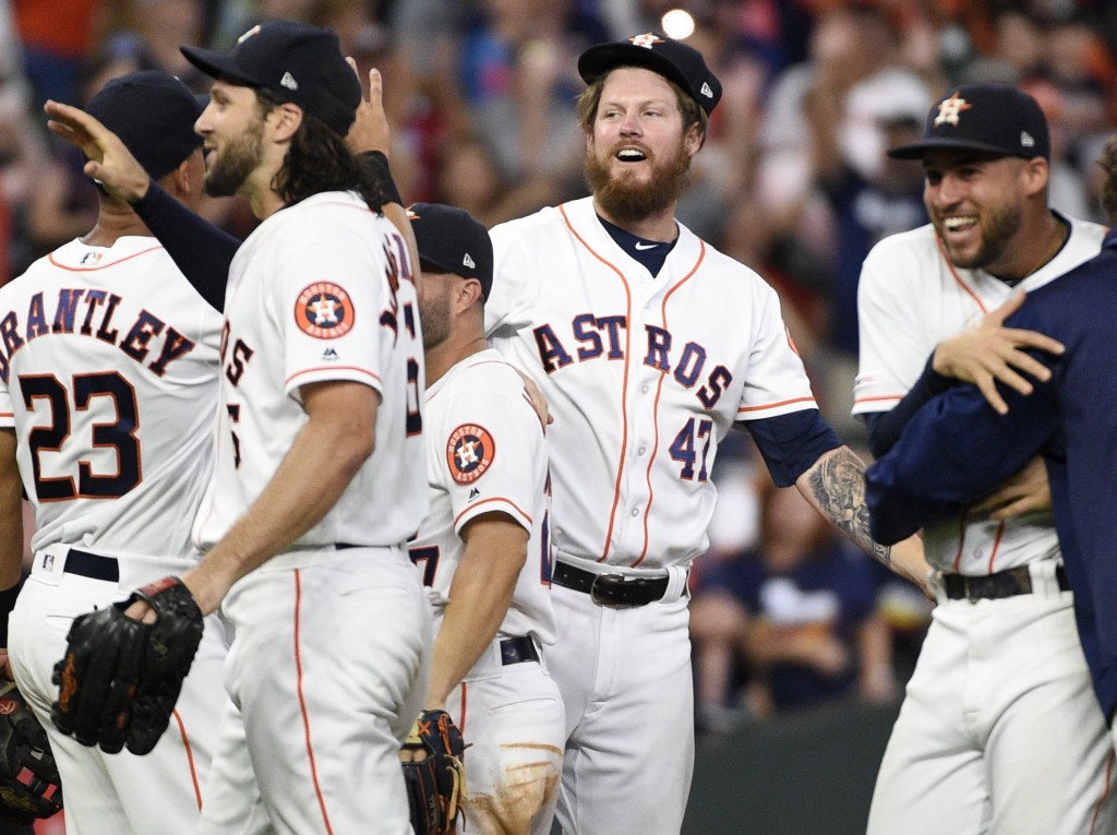 Houston Astros relief pitcher Chris Devenski, second from right, and teammates celebrate the team's 9-0 win over the Seattle Mariners, with a four-pit...