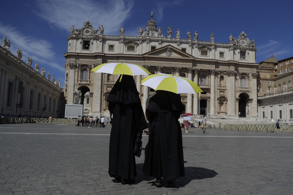 Nuns shelters from the sun with their umbrellas bearing the colors of the Vatican flag prior to the start of Pope Francis Angelus prayer in St. Peter'...