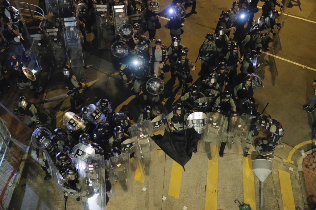 An umbrella is thrown at riot police during a confrontation in Wong Tai Sin district in Hong Kong on Saturday, Aug. 3, 2019. Protesters and authoritie...