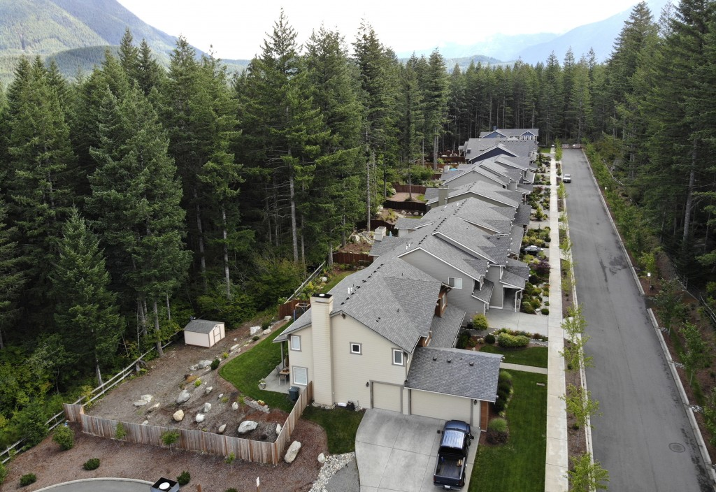 In this photo taken July 24, 2019, a block of houses is surrounded on three sides by a forest in the Cascade foothills of North Bend, Wash. Experts sa...