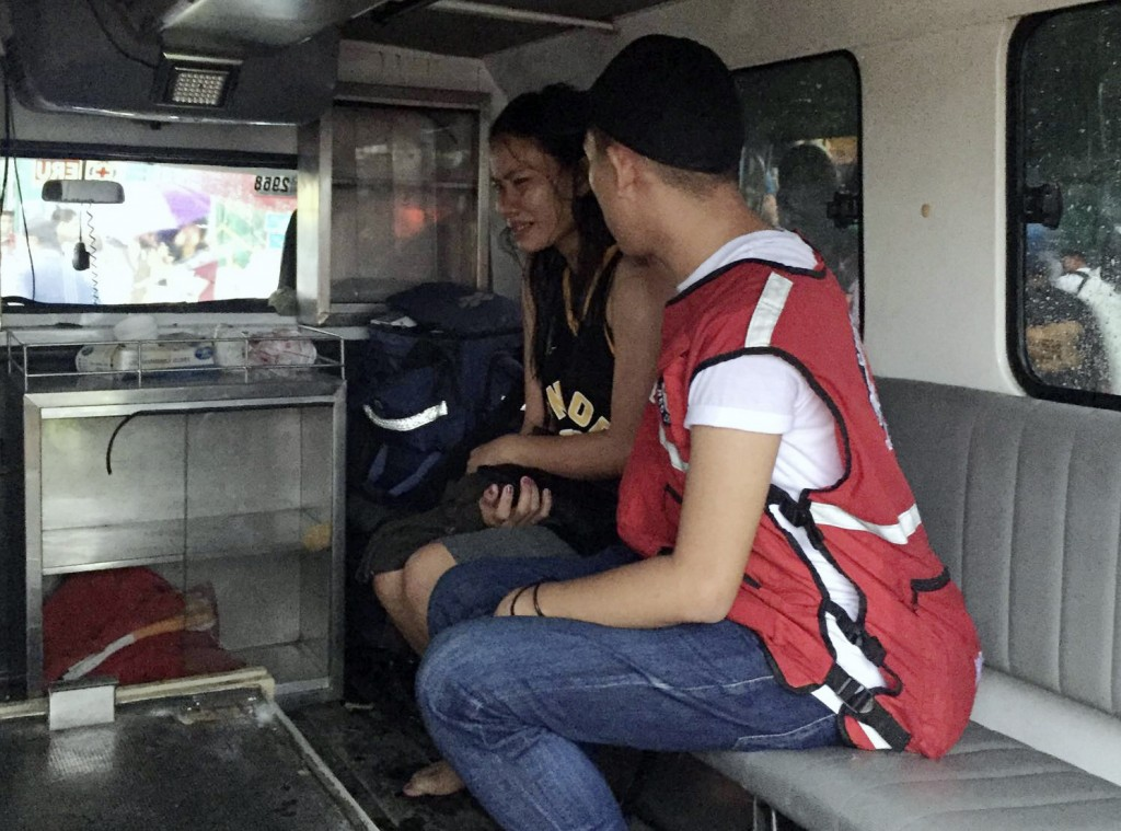 In this photo provided by the Philippine Red Cross, a rescue worker talks to a crying survivor after their ferry boat capsized due to bad weather in t...