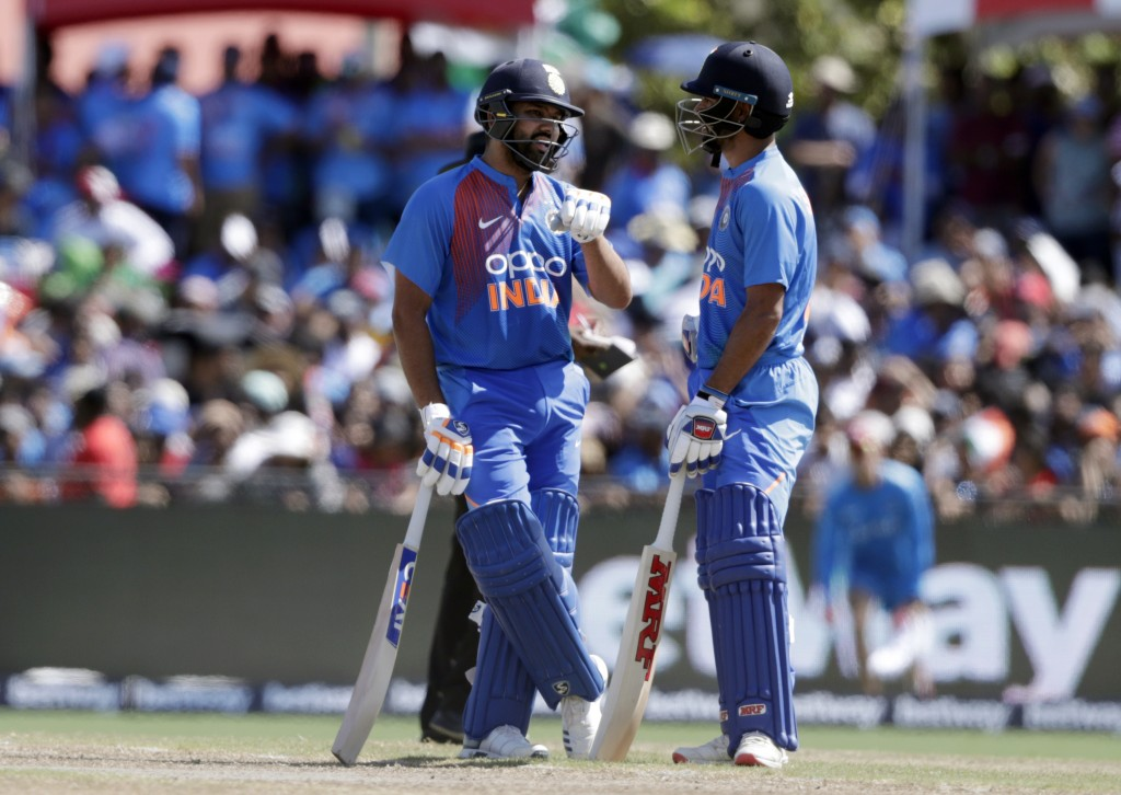 India's Rohit Sharma, left, and Shikhar Dhawan, right, talk during the second Twenty20 international cricket match against the West Indies, Sunday, Au...