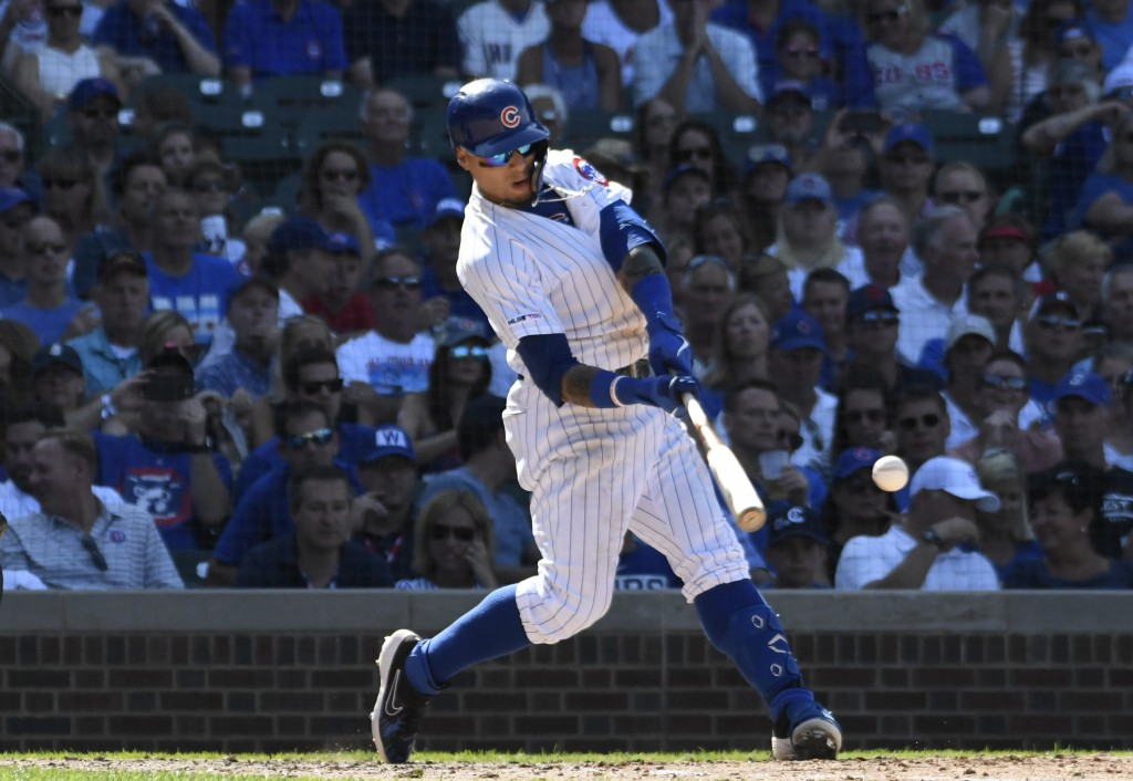 Chicago Cubs' Javier Baez (9) hits a one run single against the Milwaukee Brewers during the eighth inning of a baseball game, Saturday, Aug. 3, 2019,...