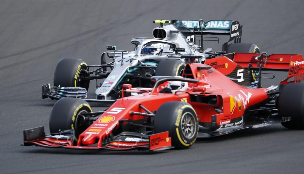 Ferrari driver Sebastian Vettel, bottom, of Germany, leads Mercedes driver Valtteri Bottas, foreground, of Finland, during the Hungarian Formula One G