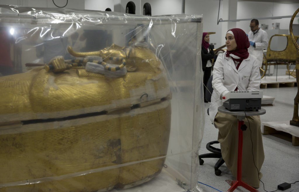 The gold-covered sarcophagus of King Tutankhamun is encased in a tent for restoration procedures at the conservation center of the the Grand Egyptian
