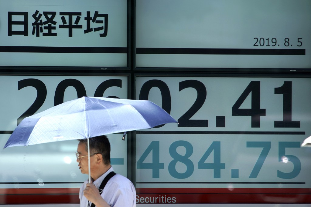A man with a parasol walks past an electronic stock board showing Japan's Nikkei 225 index at a securities firm in Tokyo Monday, Aug. 5, 2019. Asian s...