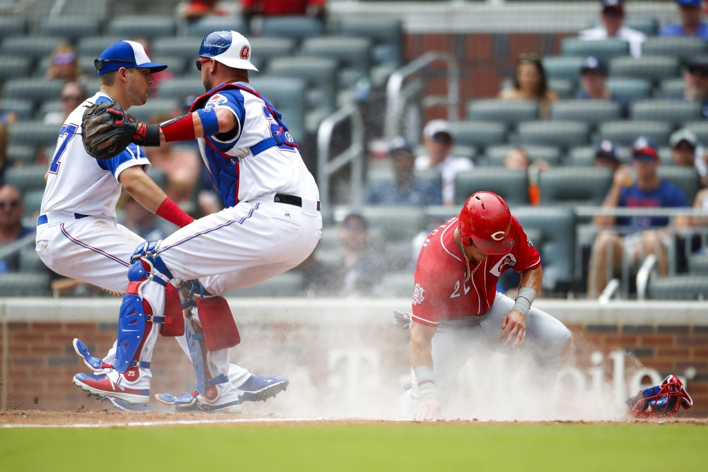 Cincinnati Reds Derek Dietrich (22) slides into home to score off a sacrifice bunt of Sonny Gray in the fourth inning of a baseball game against the A...