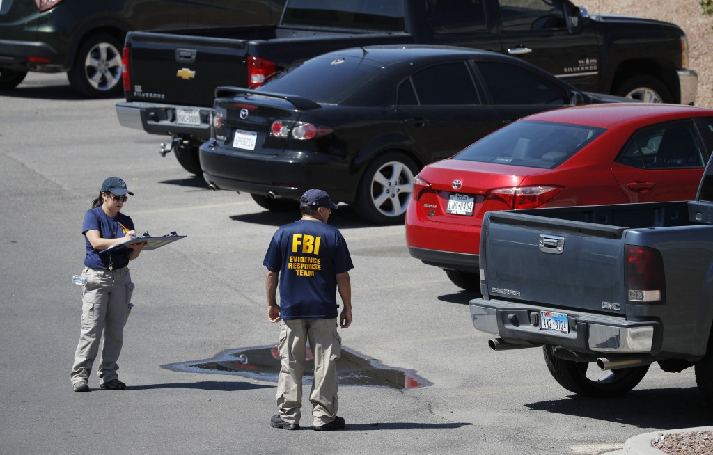 Members of the FBI evidence response team investigate the scene of a mass shooting at a shopping complex Sunday, Aug. 4, 2019, in El Paso, Texas. (AP