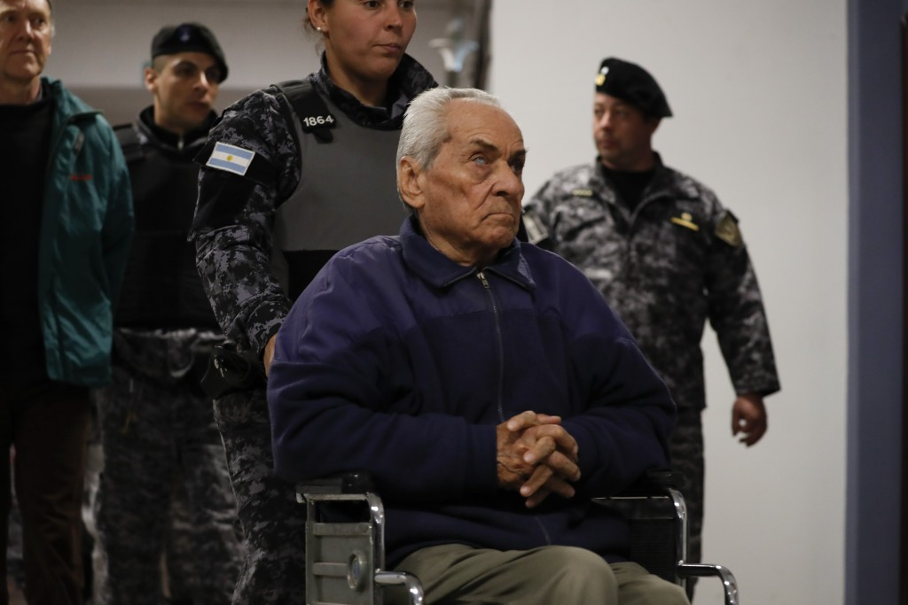 Rev. Nicola Corradi is escorted from a courtroom after attending his trial in Mendoza, Argentina, Monday, Aug. 5, 2019. Corradi, an Italian who is 83 ...