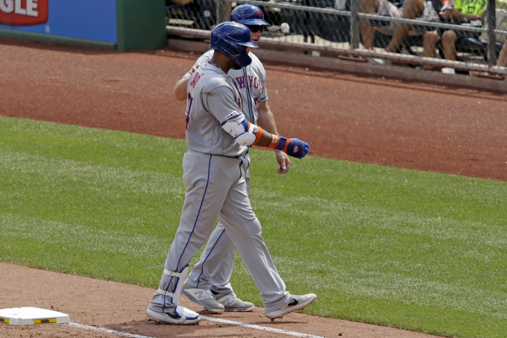 New York Mets' Robinson Cano, front, is helped off the field by first base coach Glenn Sherlock, back, during the fourth inning of a baseball game aga...