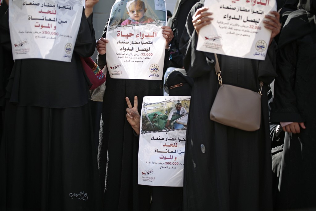 """FILE - In this Dec. 10, 2018 file photo, Yemeni women hold banners in Arabic that read, in part, """"Open Sanaa airport to limit the suffering and deaths..."""