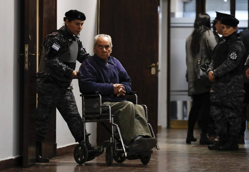 Rev. Nicola Corradi is escorted from a courtroom after attending his trial in Mendoza, Argentina, Monday, Aug. 5, 2019. Corradi, an Italian who is 83