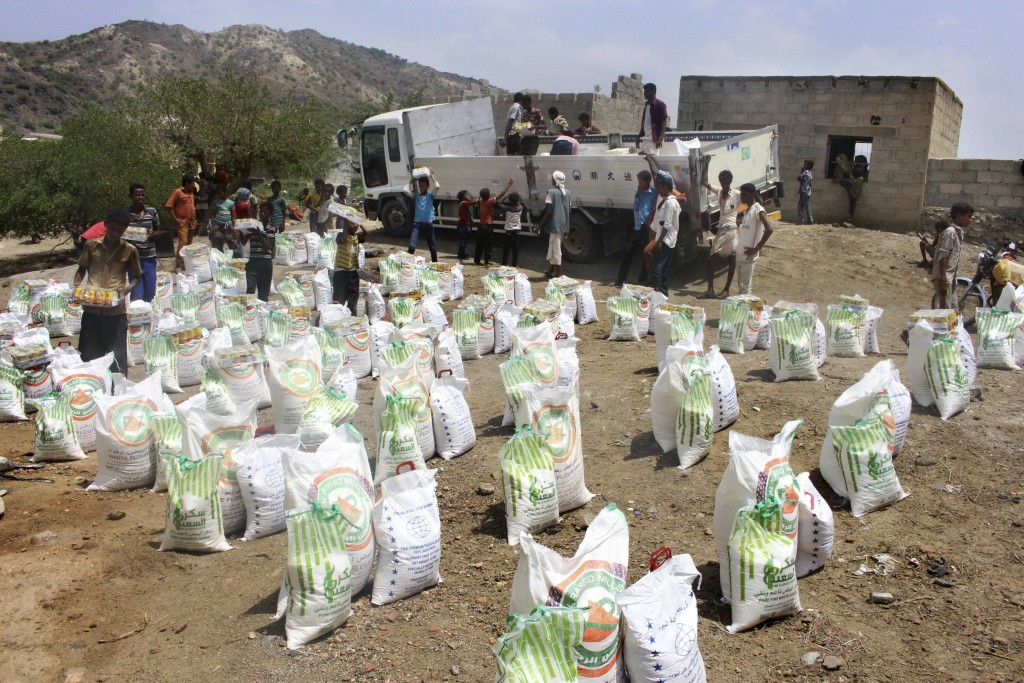FILE - In this Sept. 23, 2018 file photo, men deliver aid donations from donors, in Aslam, Hajjah, Yemen. An Associated Press investigation found some
