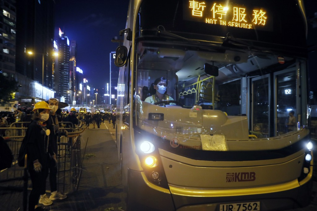An off duty bus drives pass a barricades by protesters at Causeway Bay to hold the anti-extradition bill protest in Hong Kong, Sunday, Aug. 4, 2019. T...