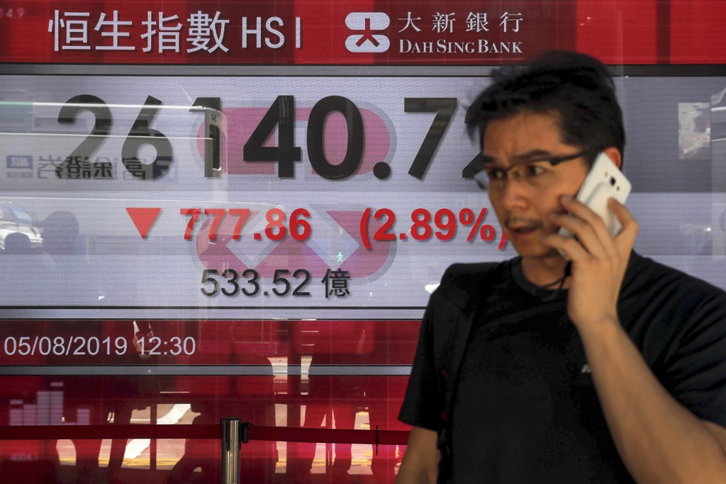A man uses his smartphone walks by an electronic board showing Hong Kong composite index outside a bank in Hong Kong, Monday, Aug. 5, 2019. Asian stoc...