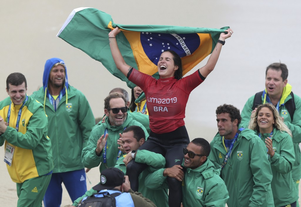 Chloe Calmon of Brazil celebrates wining the gold for longboard in the women's SUP surfing final at the Pan American Games on Punta Rocas beach in Lim