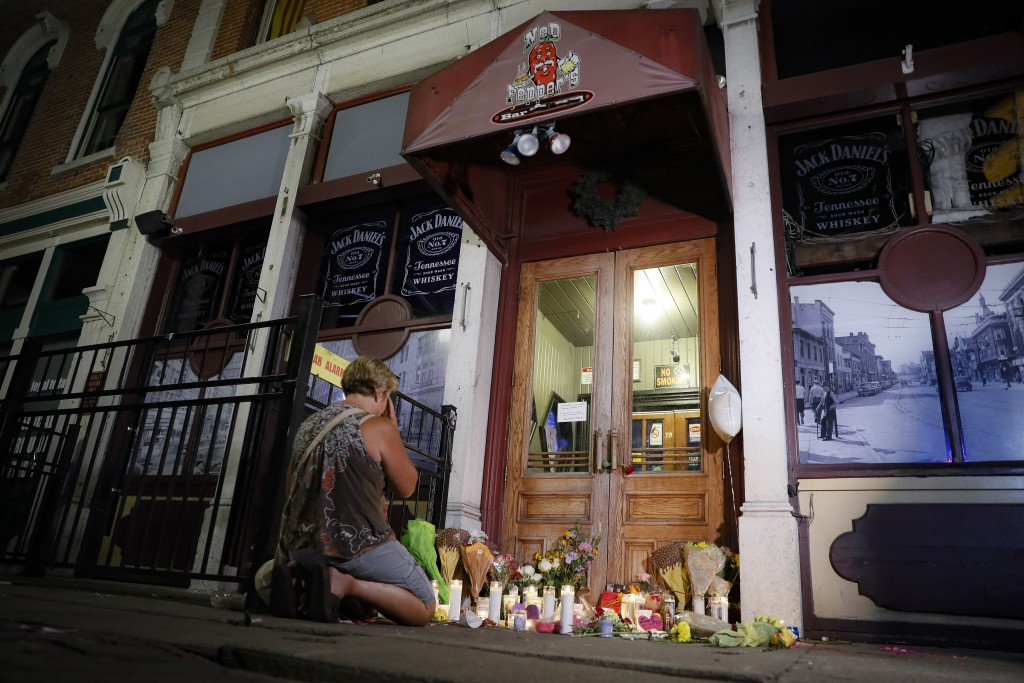Mourners visit a makeshift memorial outside Ned Peppers bar following a vigil at the scene of a mass shooting, Sunday, Aug. 4, 2019, in Dayton, Ohio. ...