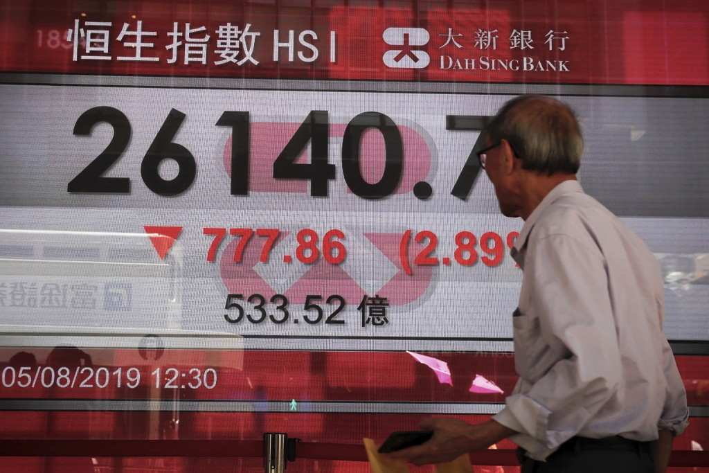 An elderly man looks at an electronic board showing Hong Kong composite index outside a bank in Hong Kong, Monday, Aug. 5, 2019. Asian stock markets f...