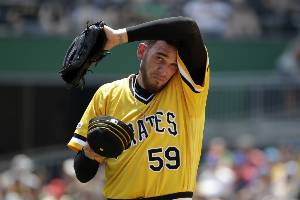 Pittsburgh Pirates starting pitcher Joe Musgrove wipes his head after giving up a two-run home run during the first inning of a baseball game against