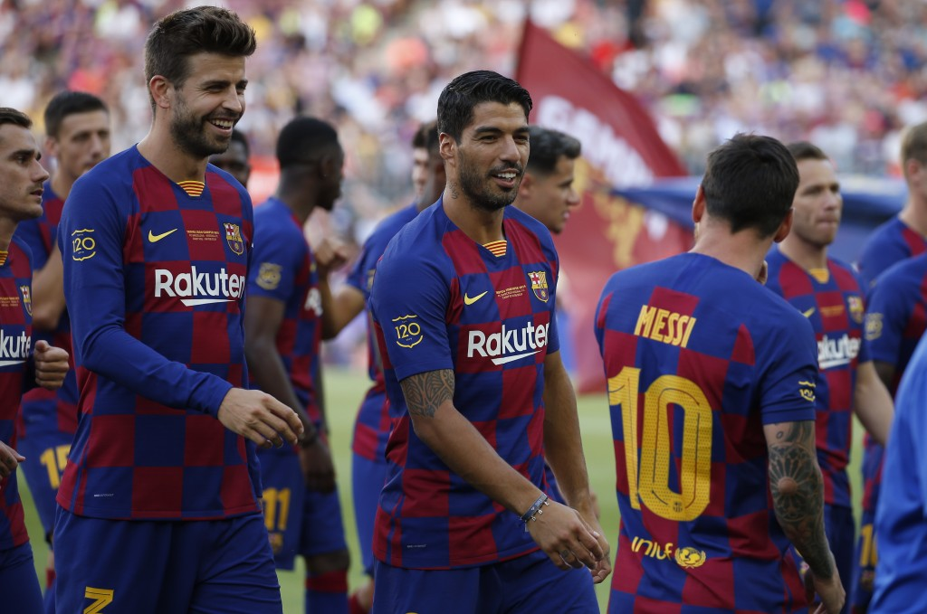 FC Barcelona's Luis Suarez, center, talks with his teammate Lionel Messi, right, prior of the Joan Gamper trophy soccer match between FC Barcelona and...