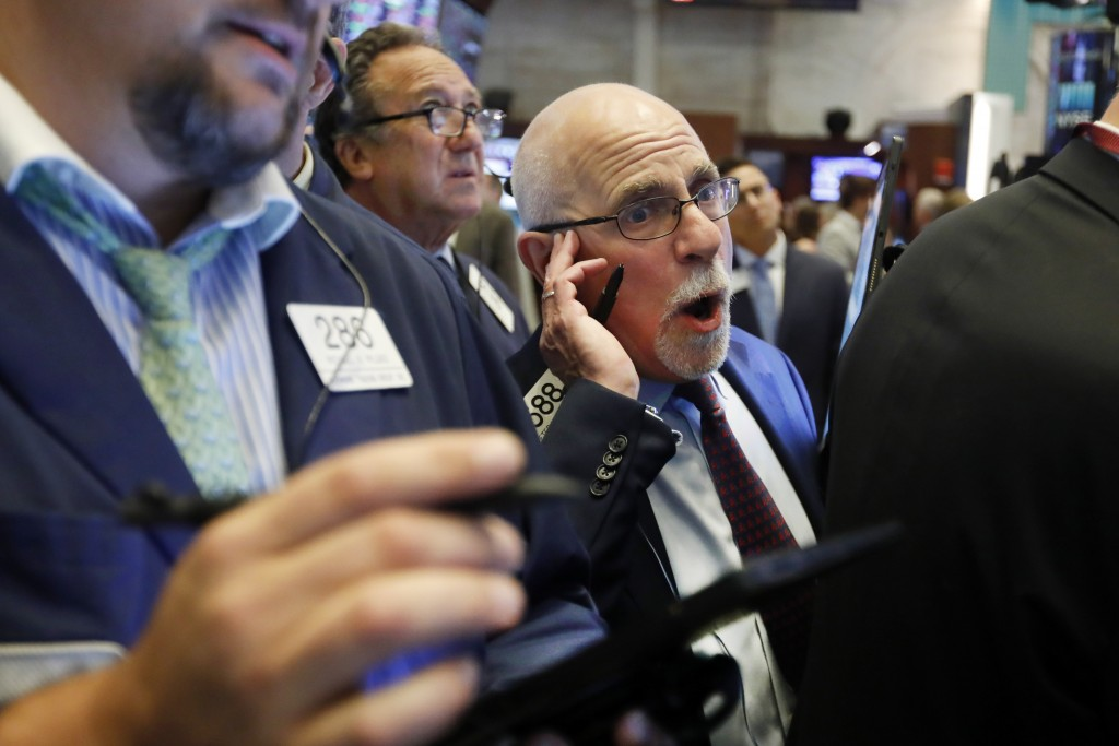 FILE - In this July 30, 2019, file photo trader Peter Tuchman, center, works on the floor of the New York Stock Exchange. The U.S. stock market opens ...