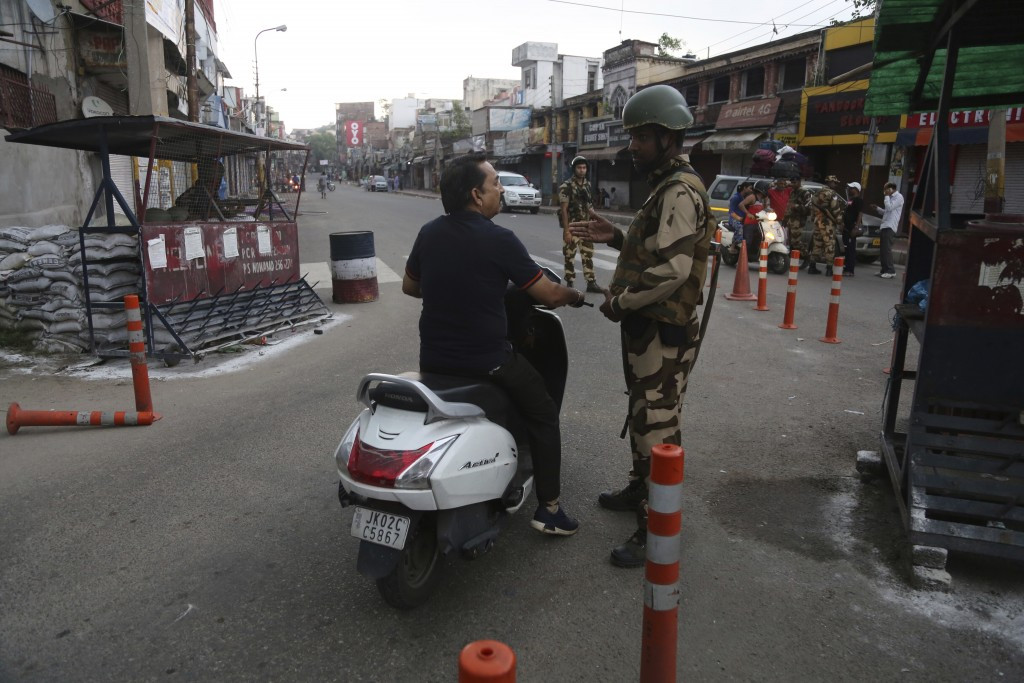 An Indian paramilitary soldier stops a commuter during curfew like restrictions in Jammu, India, Monday, Aug. 5, 2019. An indefinite security lockdown