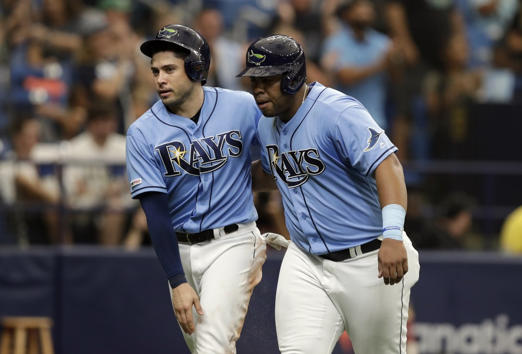 Tampa Bay Rays' Travis d'Arnaud, left, and Jesus Aguilar celebrate after scoring on a two-run double by Avisail Garcia off Miami Marlins relief pitche...