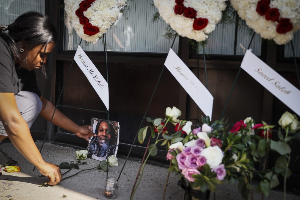 "Jamila McNichols, sister of slain mass shooting victim Thomas ""TJ"" McNichols, mourns beside a memorial near the scene of the mass shooting Monday, Aug"