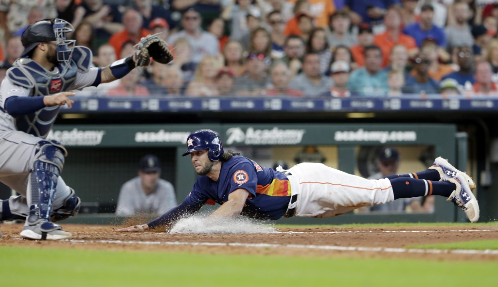 Seattle Mariners catcher Omar Narvaez, left, waits for the ball as Houston Astros' Jake Marisnick, right, dives safely for the plate on the sacrifice
