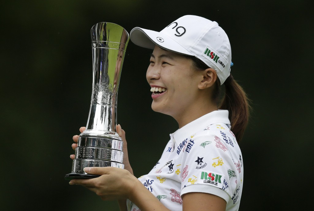 Japan's Hinako Shibuno smiles as he holds the trophy as she celebrates after winning the Women's British Open golf championship at Woburn Gold Club ne