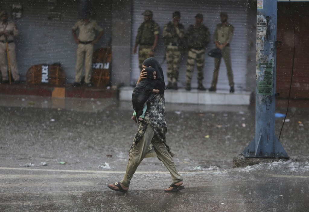 A woman carries her child as she walks past Indian security personnel as it rains during curfew like restrictions in Jammu, India, Monday, Aug. 5, 201...