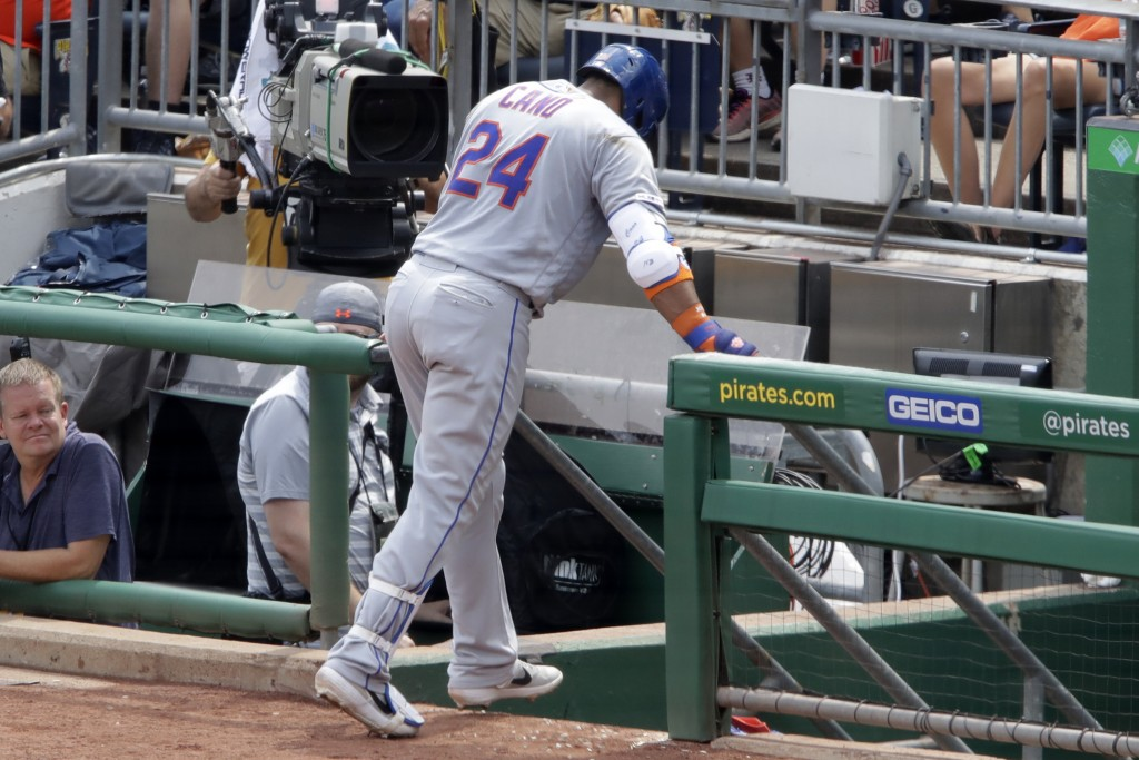 New York Mets' Robinson Cano makes his way to the dugout after injuring his left hamstring while rounding first base during the fourth inning of a bas...