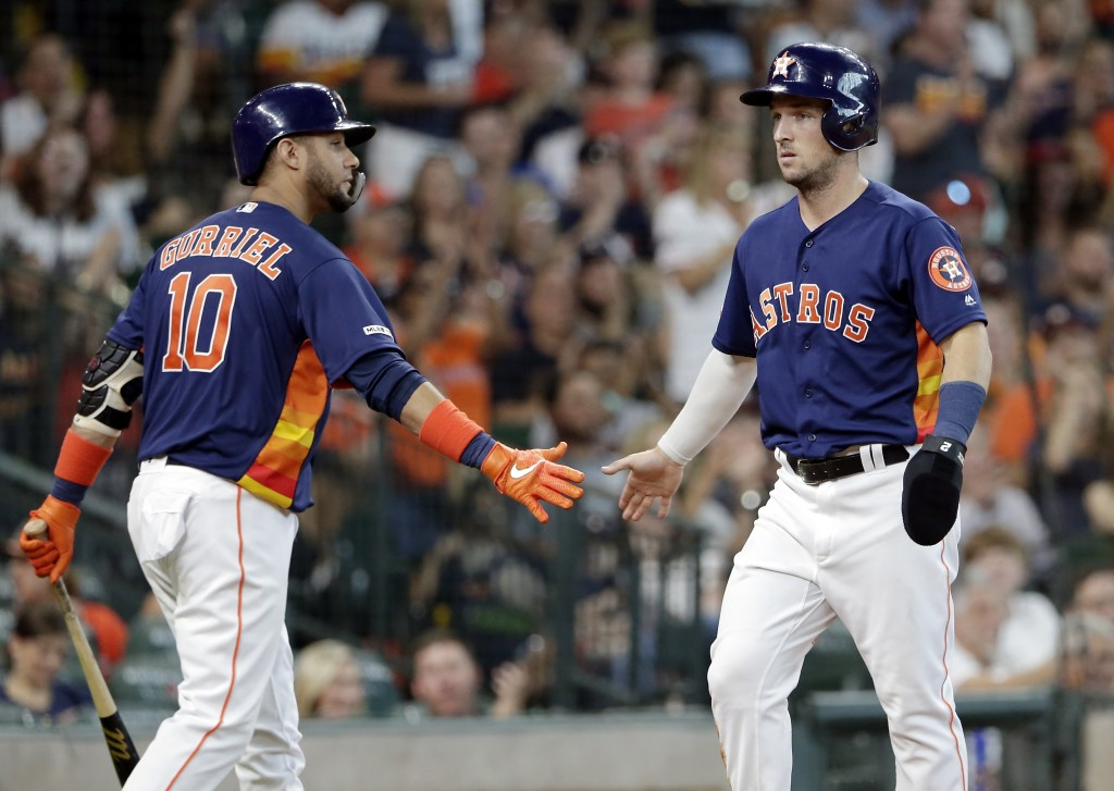 Houston Astros first baseman Yuli Gurriel (10) congratulates Alex Bregmam, right, after he scored on the hit by Carlos Correa during the fourth inning...