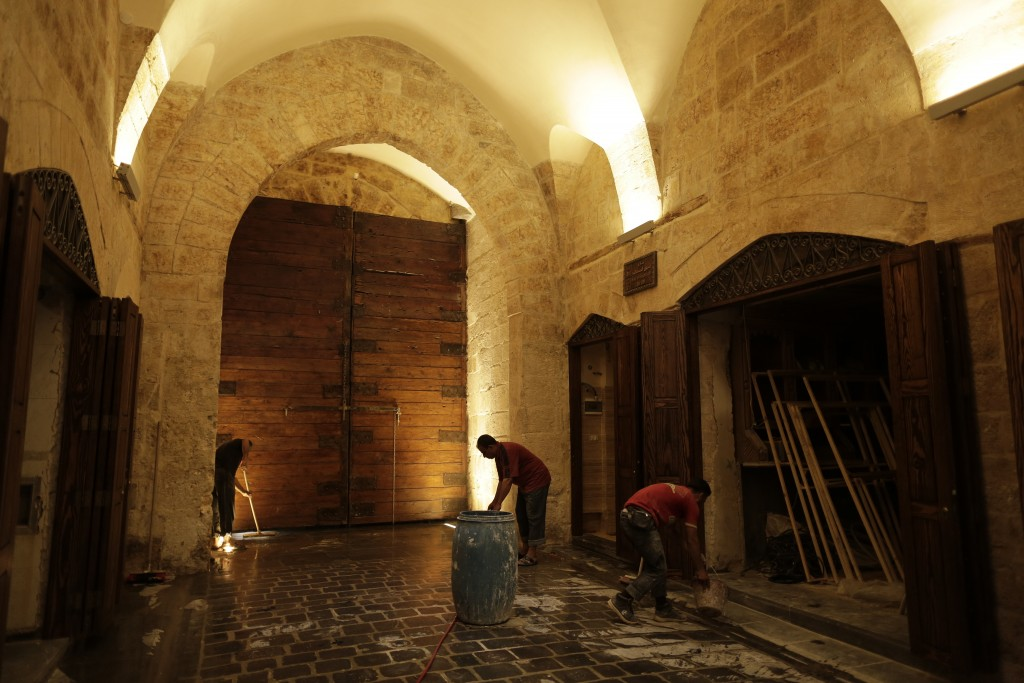 In this Saturday, July 27, 2019 photo, Syrian workers work on the newly renovated al-Saqatiyah Market in the old city of Aleppo, Syria. Much of Aleppo