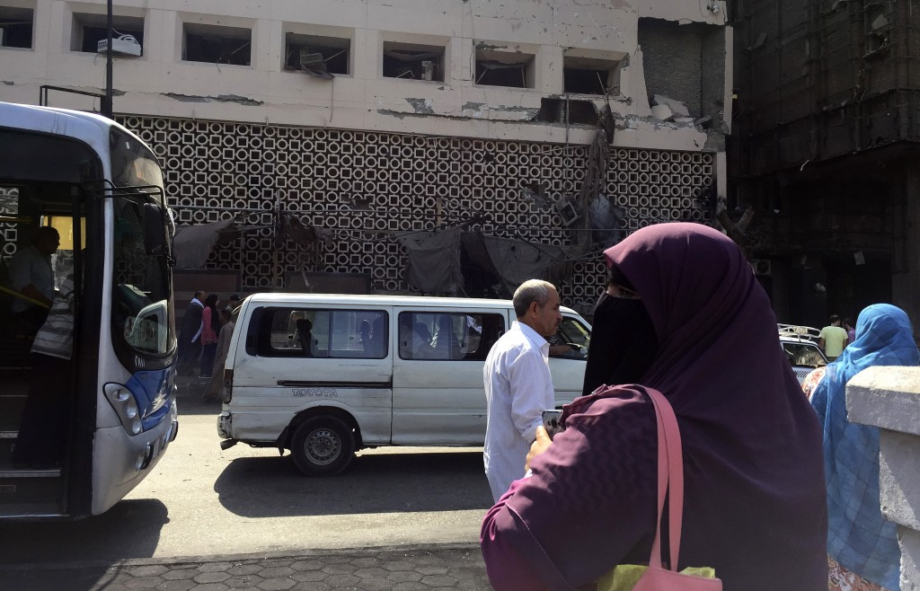 People survey the aftermath of a fiery car crash outside the National Cancer Institute in Cairo, Egypt, Monday, Aug. 5, 2019. The multiple-car crash s...
