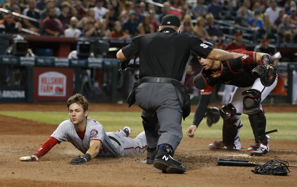 Washington Nationals' Trea Turner, left, scores a run on a ball hit by Anthony Rendon in the seventh inning during a baseball game against the Arizona