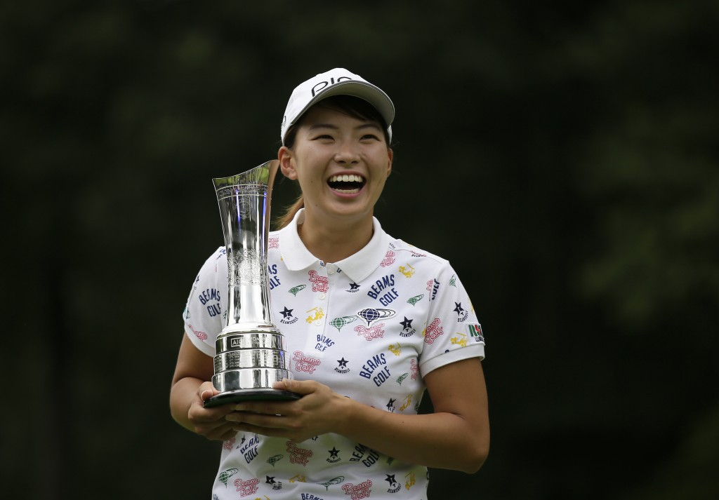 Japan's Hinako Shibuno reacts as she holds the trophy as she celebrates after winning the Women's British Open golf championship at Woburn Gold Club n...